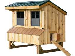 This chicken coop features cedar board and batten siding, metal roof, nesting boxes, and windows.