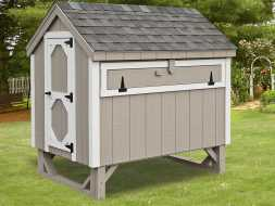 This backyard chicken coupe features, vertical painted gray siding and white trim, has large door for easy access to clean.