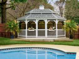 This large gazebo features vinyl construction, oval octagonal shape with a shingled roof.