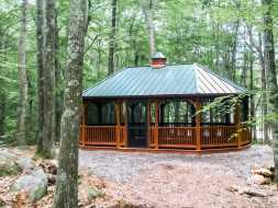 This cedar stained wood gazebo features metal roof, and screens, offers lots of room to entertain or just relax.