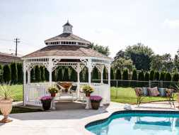 This white octagon gazebo has pagoda design roof with cupola accent, and victorian style trim, perfect addition to any pool area.