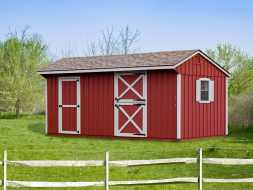 This horse barn has red painted vertical siding with shingle roof, and white trim, plus window shutters.