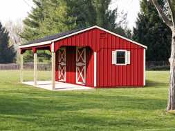 Horse barn featuring red painted vertical wood siding with white trim, and black shingle roof.