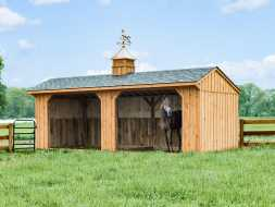 This horse barn structure features a open shed design with cedar siding, shingle roof, and cupola accent.