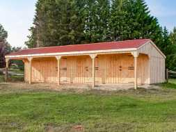 Horse Barn with red metal roof, 3 stalls plus a tack room, with porch overhang.