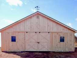 This large horse barn has lots of space with large double sliding door, windows, and metal roof with cedar vertical siding.