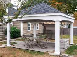 This outdoor pavilion built on patio with vinyl columns and shingled roof.