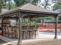 This wood pavilion is stained, and has shingled hip roof, plus bar area.