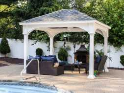 This backyard pavilion has vinyl construction, built on the pool deck, and exposed rafter design,
