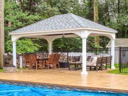 Outdoor pavilion with white vinyl wrapped columns, hip roof, and next to the pool.