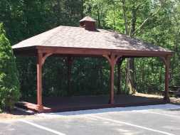 Pavilion is constructed with stained wood and shingle roof, with cupola accent.