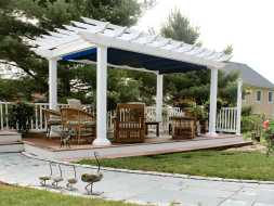This vinyl pergola is built on a deck and features scalloped rafter tails and an ez shade.