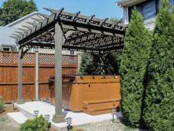 Stained wood pergola features scalloped rafter tails, and creates beautiful addition to the deck.