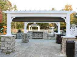This personalized patio gazebo is made with vinyl construction, includes ez shade and sports custom rock column bases.
