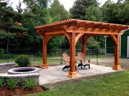 This stained wood pergola has lasting good looks, makes a enjoyable place to relax in the sun.