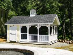 This pool house features screened in area with storage, vinyl siding exterior and a cupola accent.