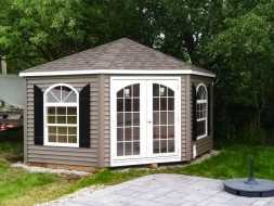 Pool house featuring octagonal shape, vinyl siding, shingled roof, and custom windows.