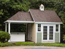 This poolhouse is personalized with multi color siding exterior, attached covered bar area, plus inside sitting area, with cupola accent.