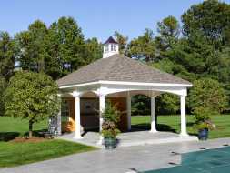 Pool House featuring white vinyl columns, shingled hip roof, and a cupola accent.