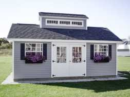 Storage shed featuring vinyl siding, double 9 lite door, shingle roof, custom cupola, and window boxes.