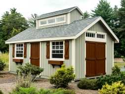 Personalized storage shed accented with barn style doors, transom windows and a custom cupola.