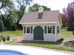 This custom shed features arched top doors, window shutters, and a cupola.