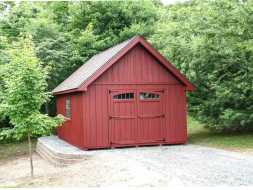 Personalized wood storage shed with painted red vertical siding, gable shingle roof, and transom windows in the doors.