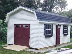 This vinyl storage shed has a gambrel shingled roof, double end door with a ramp and window boxes.