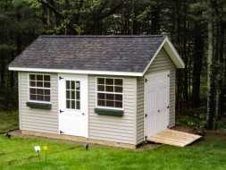 This small outdoor storage shed features window boxes, large windows, and double raised panel doors with ramp.