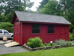 This backyard storage shed features red painted vertical siding, gable roof, and lawn tractor ramp.