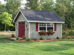 This custom shed features vertical siding window boxes, transom windows in double doors.