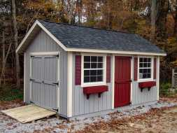 This storage shed features vertical painted siding, window shutter and boxes, & a ramp.