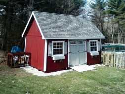 This wood storage shed features vertical red painted siding with gray shingle roof, and accented with window shutters and transom window doors.