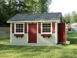 Shed featuring red painted doors with green siding, plus a ramp, and sits on crushed stone foundation.