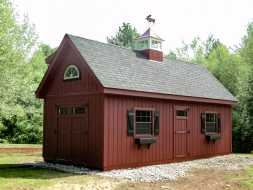This custom storage shed is personalized with transom window doors, window shutters and boxes, and a cupola with a weathervane.