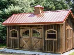 This wooden storage shed has custom cedar stained siding, with metal roof and a cupola.