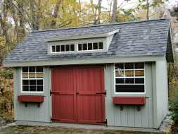 This unique garden shed features a transom winow dormer, double shed style doors and window boxes.
