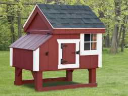 This small red painted chicken coop will look well anywhere and looks good with white trim and a black shingled roof.
