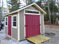This shed features vinyl siding and double shed doors with transom window and shingle roof.