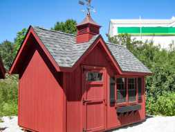 Shed has a unique design with steep roof and gable over the door a cupola accent, all painted red with gray  shingles and black window box and shutters