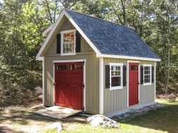 This shed is larger and has vertical painted siding, double shed doors with equipment ramp and has window shutters.