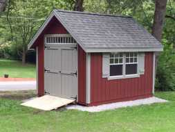 This smaller storage shed features vertical red painted siding, shingle roof and windows with shutters plus a transom window over the double shed door.