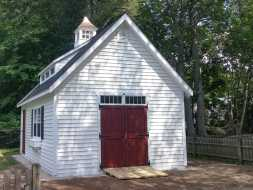 This backyard storage shed has vinyl siding exterior and double shed doors along with a shed style dormer and a cupola.
