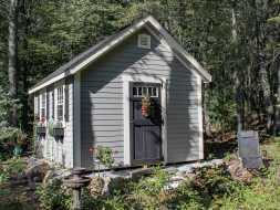 Shed featuring gray vinyl siding and custom door and window options.