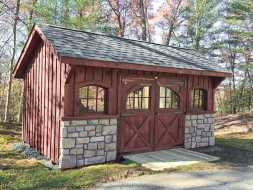 This custom shed features board and batten siding painted red arched top windows and has rock wainscot on the front.