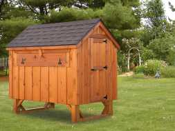 This chicken coop is built with stained cedar board exterior plus a shingle roof and is elevated off the ground for easy access.