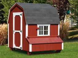 This barn style chicken coop is designed to look like a barn with its red paint and white trim and gambrel shingled roof.