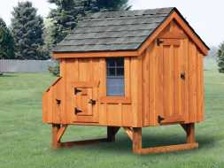 This backyard chicken coop features cedar siding, shingle roof, and is elevated from the ground.