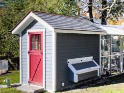 This chicken coop features gray vinyl siding a red walk door and shingled roof plus has white trim.
