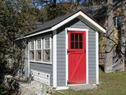 This chicken coop is custom built with extra windows, vinyl siding, and a red painted  lite door.